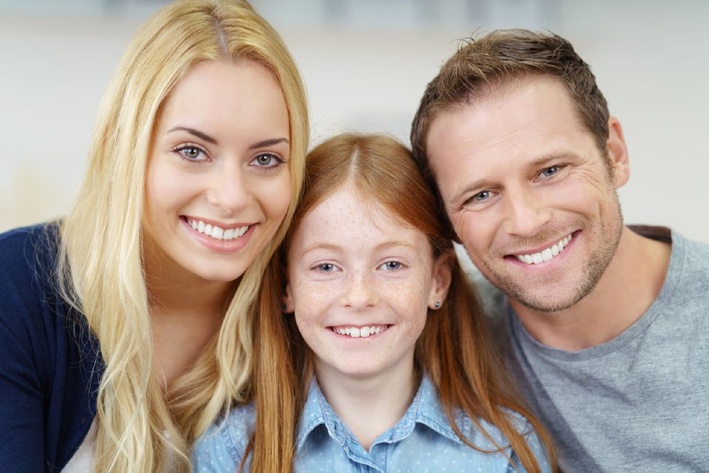 52361627 - smiling portrait of a happy young family with a pretty small redhead girl flanked by her parents posing close together for the camera